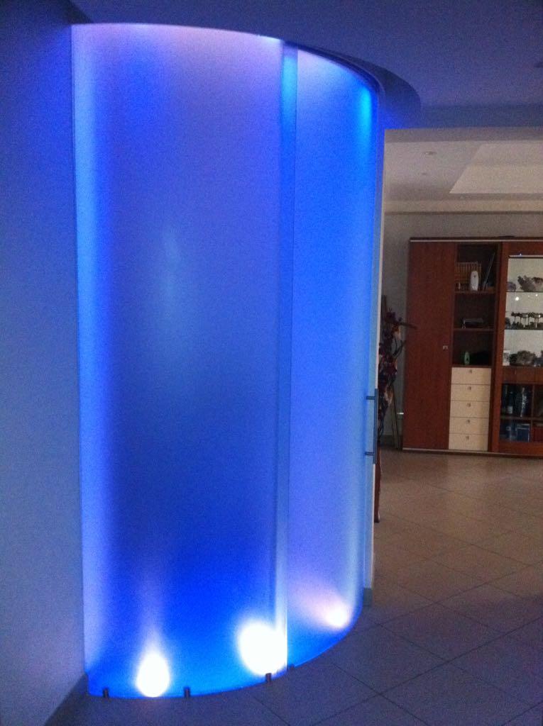 Realizzazione di una vetrata divisoria in cristallo curvo con sistema scorrevole e illuminazione interna a led multicolori